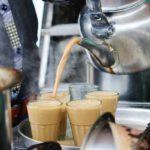 Процесс наливания чая масала в стаканы из чайника