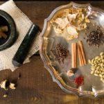 Специи для чая масала на подносе и ступа