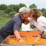Пара целуется во время мытья облепихи
