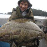 Мальчик держит в руках большого палтуса