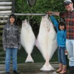 Отец и двое детей с пойманными палтусами