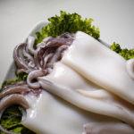 свежий очищенный кальмар на листьях салата