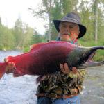 мужчина с красным лососем в руках