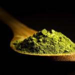порошок зеленого чая матча на деревянной ложке