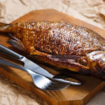 копченая рыба на доске, столовые приборы