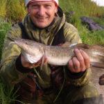 налим в руках рыбака